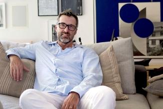 Kai Loebach sitting on a sofa in his living room