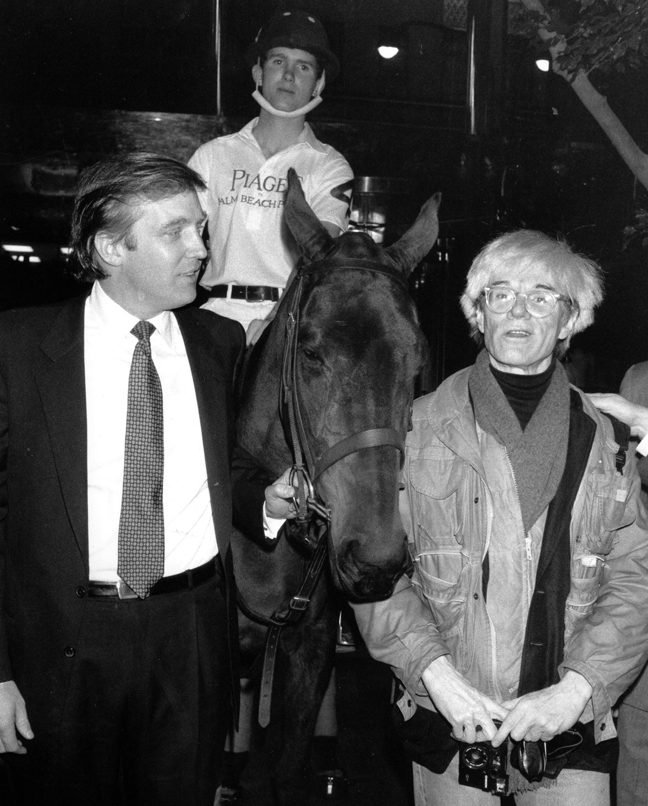 Donald Trump owner of New York's Trump Tower, holds the bridle of a polo pony while talking to Andy Warhol. Image: Mario Suriani