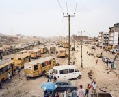 Danfos and Moules (private bus-taxi) at the Badagry Road expansion projekt at the Odun Ade bus stop, Lagos, Nigeria