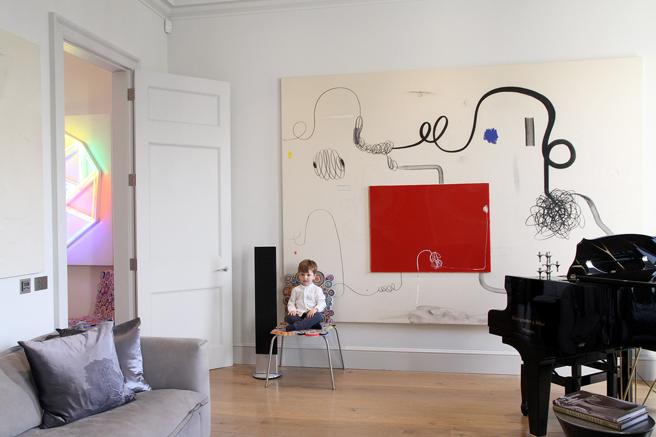 Luca sitting on a chair by the Brazilian design duo Fernando and Humberto Campana next to painting by Christian Rosa and on the left a painting by Maaike Schoorel