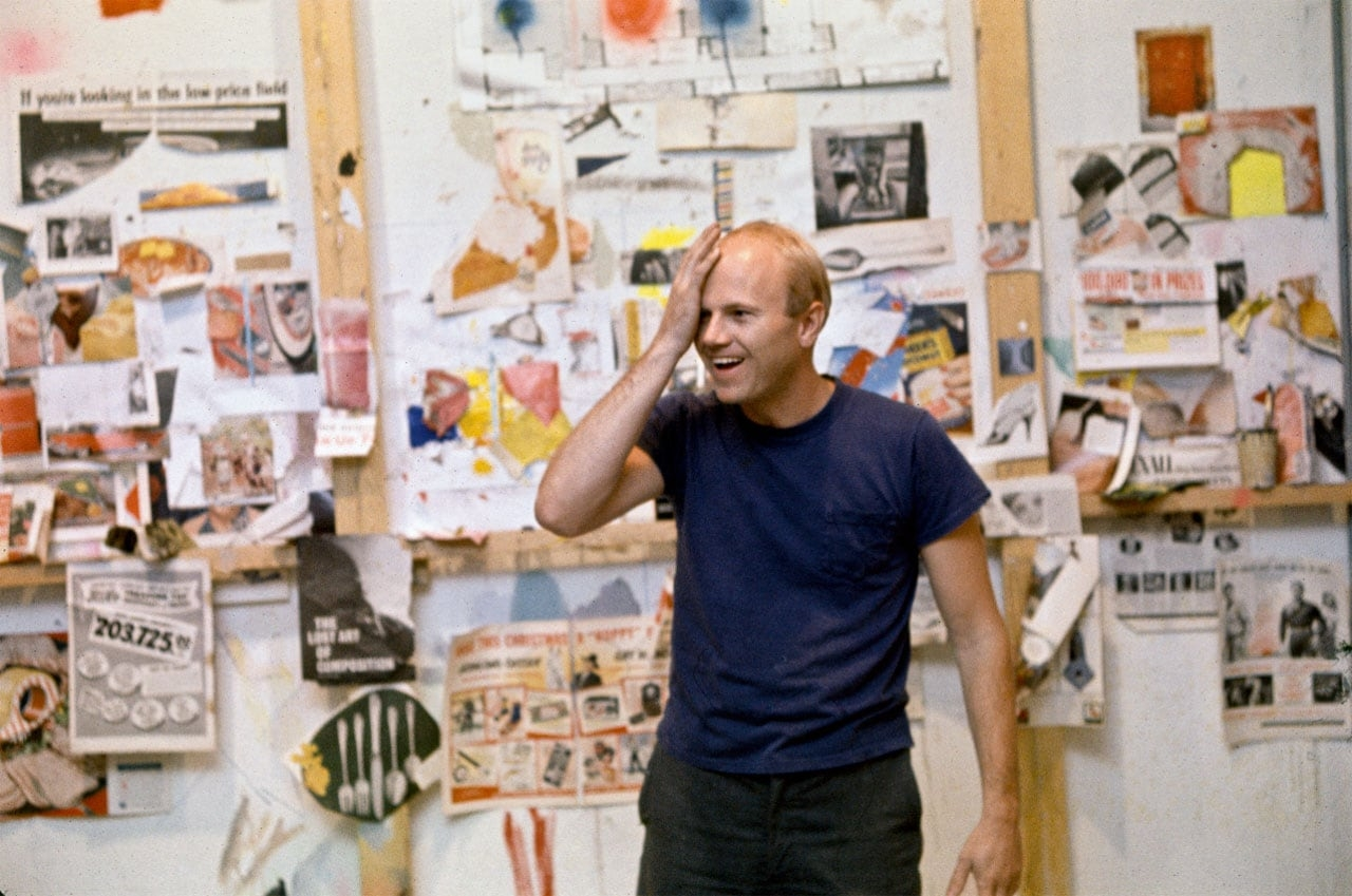 James Rosenquist in front of a wall featuring his source material in his studio in Broome Street, New York