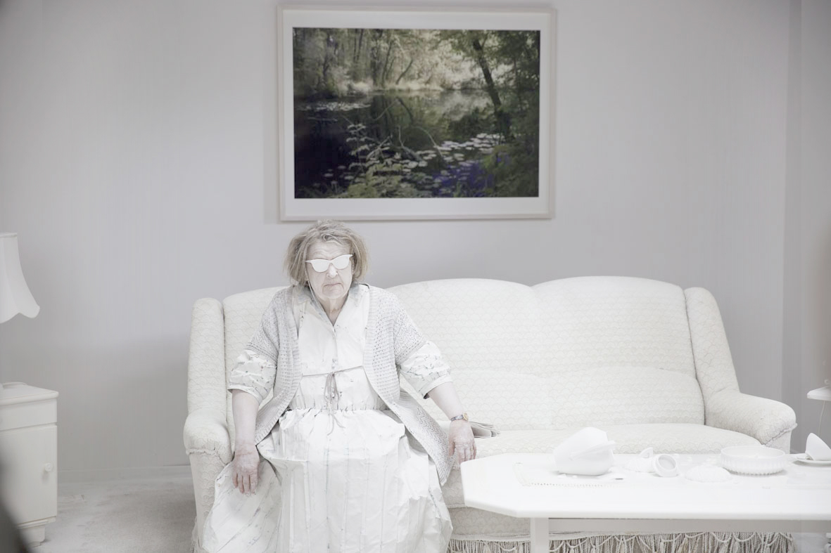 The mother, played brilliantly by Friederike Frerichs, still mildly traumatized and blinded by the white paint covering her glasses. The original artwork from Thomas Ruff's jpegs II series fits perfectly in the contemporary splendour of their new living room. Image: © Petrov Ahner